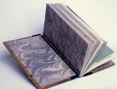 The paste downs and fly leaves are of acrylic marbled paper backed onto silk. The hinges of green silk backed to paper.