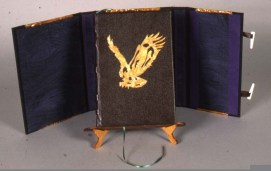 Book cover of dark brown leather over five double raised bands. The eagle is variegated copper on a leather pad and pressed into the cover.