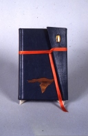 My first commission. Blue leather bound in wallet style. On cover an agate and a hand carved walnut duck. Under the cover a line gilded with variegated copper foil.
