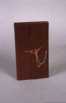 Red leather wrapper, hand carved black walnut (abstract bird) as a latch, secured with a silver chain.