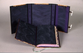 The inside of the wrapper of hand painted silk (green silk w/purple waves. The same silk was used for the paste-downs & the fly leaves (backed to moriki mulberry paper)